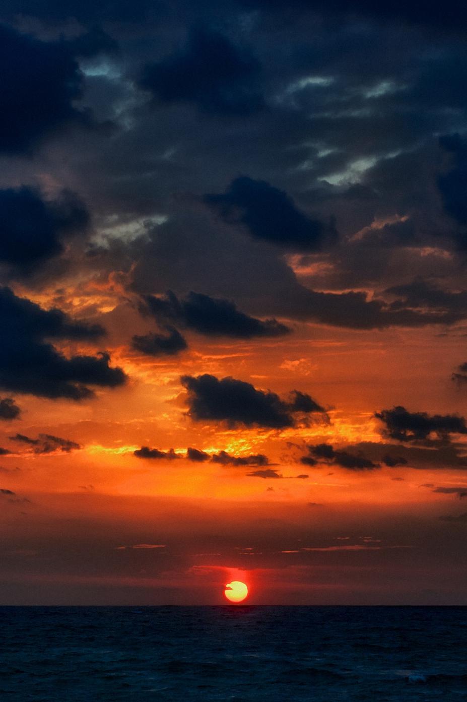 orange sunset dark clouds ocean